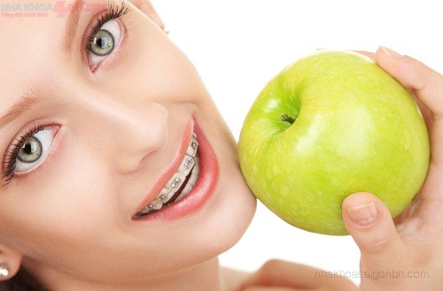 Cute girl in braces with green apple on white background